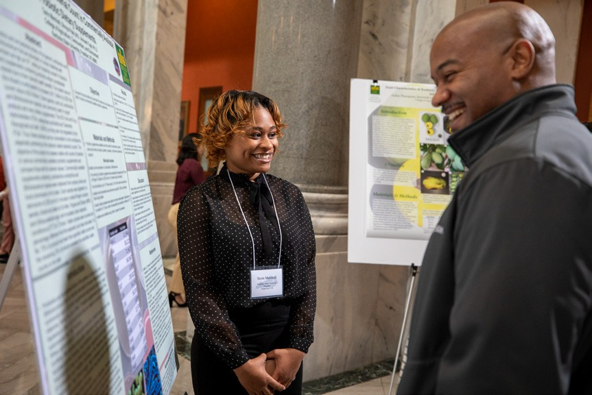 Picture of a black female student showing her poster to a black man during poster displays at the KY capital