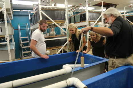 Graduate student Ben Bowman (left) and  while Dr. Jim Tidwell give legislative assistant Katelyn Conner, and field representative Regina Stivers a tour of Aquaculture Production Technology Facility.