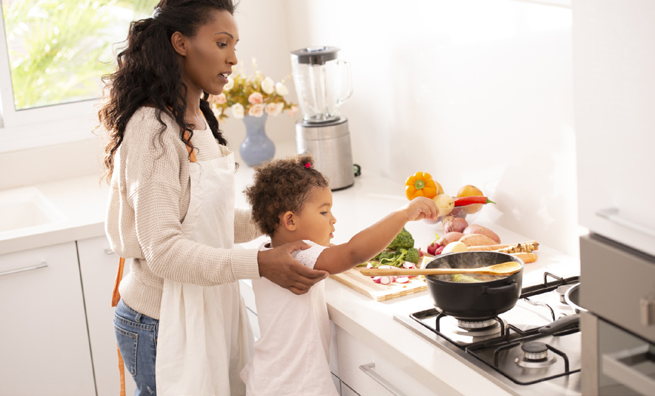 Picture of a women teaching a child to cook at the stove