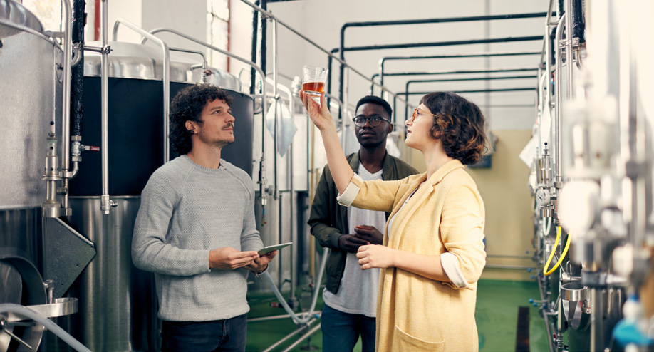 Women and two men looking at product from the Fermentation & Distillation Process