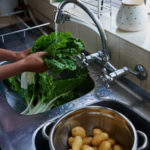 Picture of person washing green vegs in the left and potatos in the right sink